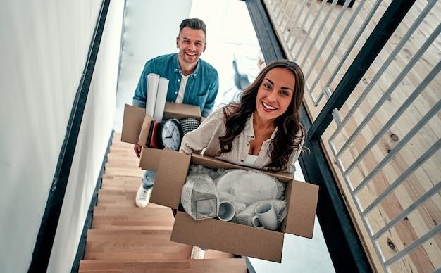 Молодая счастливая пара переезжает в новый дом. они приносят коробки с вещами в свой новый дом наверху.
