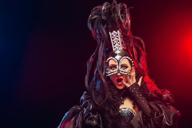 검은 스튜디오 배경에서 포즈를 취한 카니발 드레스를 입은 젊은 행복한 미소 짓는 아름다운 여성 댄서