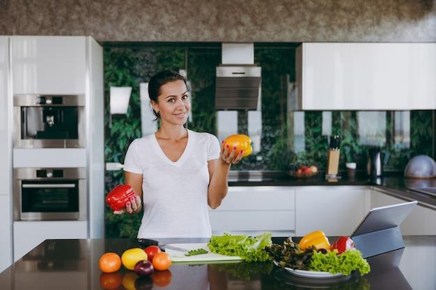テーブルの上のラップトップとキッチンで野菜を手に持って若い幸せな女性
