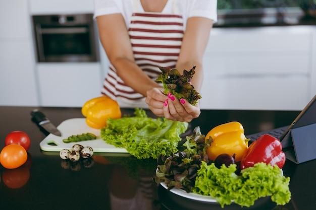 테이블에 노트북과 부엌에서 손에 야채를 들고 젊은 행복한 여자