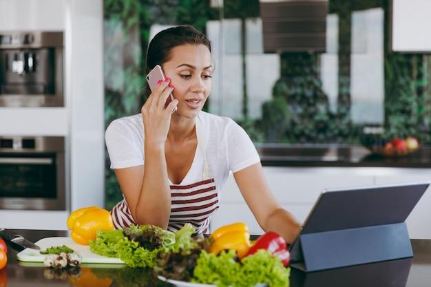 앞치마에 젊은 행복한 여자가 휴대 전화로 이야기하고 부엌에서 노트북의 조리법을보고