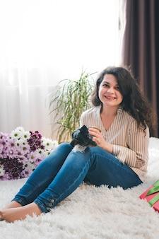 젊은 행복 한 여자는 귀여운 작은 강아지와 함께 연주. 암컷의 손에 있는 검은색과 황갈색 미니어처 핀셔