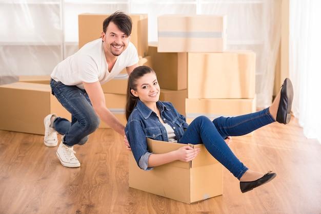 Молодая счастливая женщина, сидя в картонной коробке.