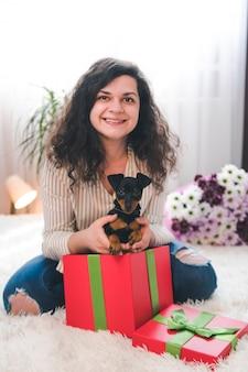 젊은 행복한 여자는 선물 상자에서 귀여운 작은 강아지를 꺼냅니다. 암컷의 손에 있는 검은색과 황갈색 미니어처 핀셔