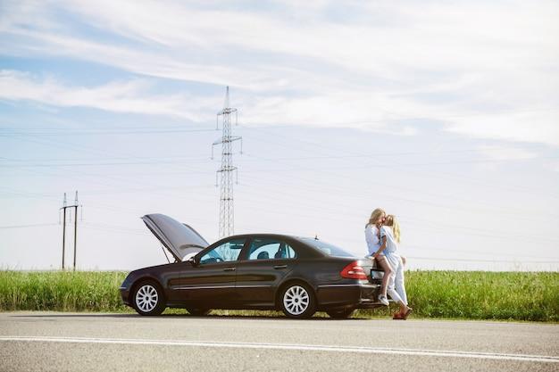 若いレズビアンのカップルは、休憩の途中で車を壊しました。車のトランクにキスして抱きしめる。関係、道路上のトラブル、休暇、休日、新婚旅行のコンセプト。