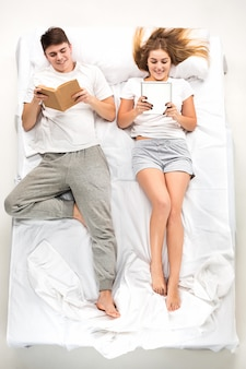 Молодая милая пара, лежа в кровати с книгами