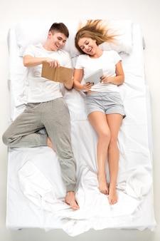 Молодая прекрасная пара, лежа в кровати с книгами