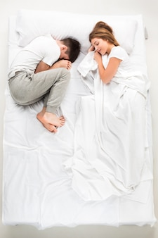Молодая прекрасная пара, лежа в белой кровати, любовь, вид сверху