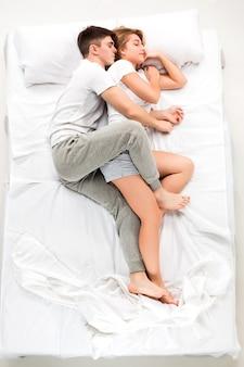 白いベッドに横たわっている素敵なカップル、愛lconcept、トップビュー