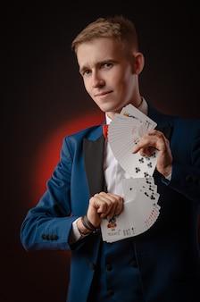 Молодой парень-волшебник держит в руках карты
