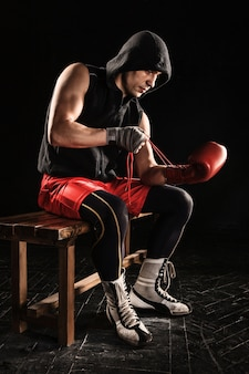Молодой спортсмен по кикбоксингу сидит и шнурует перчатку на черном
