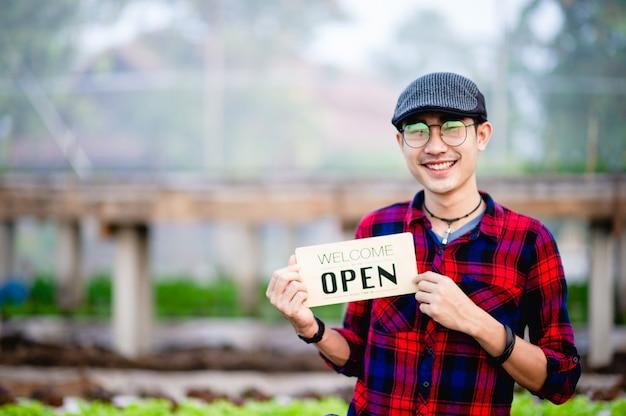 청년과 가게 개업 사인은 그의 유기농 채소밭을 방문하는 것을 환영합니다.