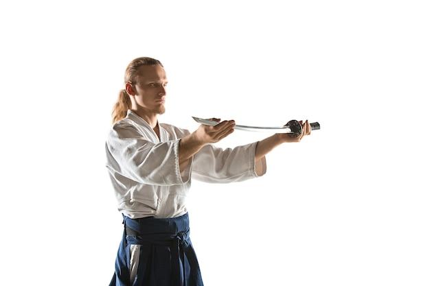 Молодой человек тренируется в айкидо в студии с саблей мастер айкидо практикует защиту