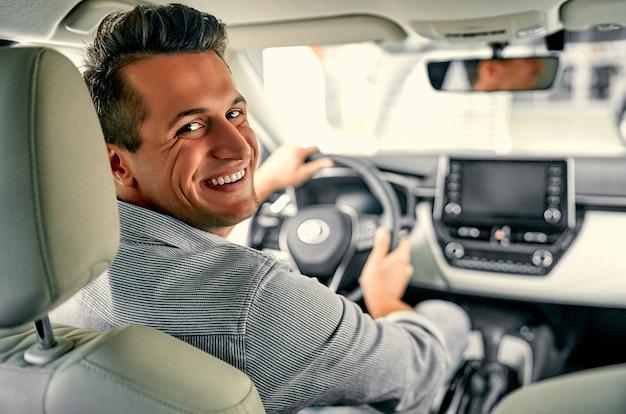 운전대 뒤에 있는 청년. 후면 보기, 카메라를 보고 그의 차를 운전 하는 젊은 남자.