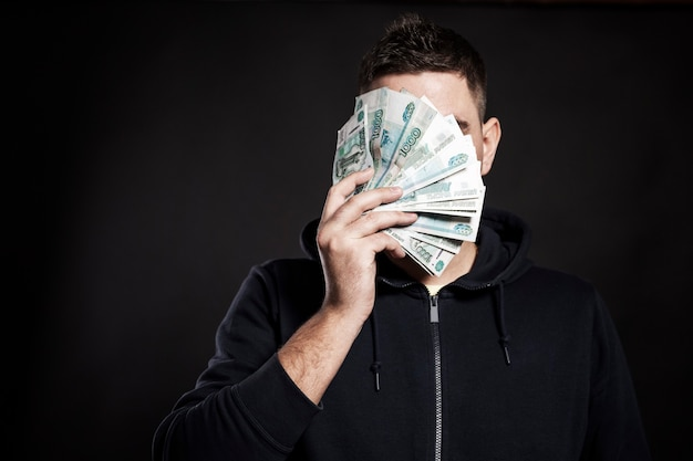 Молодой человек закрыл лицо веером банкнот. финансовый кризис и падение рубля на бирже. черный фон. крупный план. место для текста.