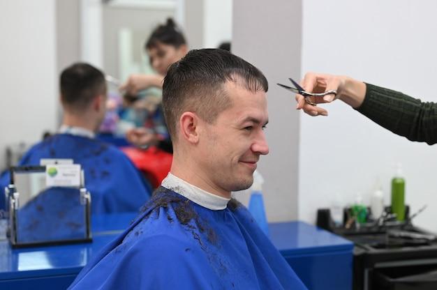 Молодой человек постригся в парикмахерской. стрижка в парикмахерской. парикмахерская