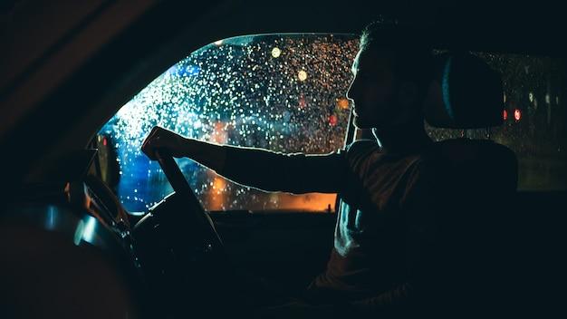 젊은 남자는 밤 비오는 길에서 차를 운전합니다