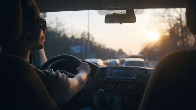街の高速道路に沿って車を運転している若い男
