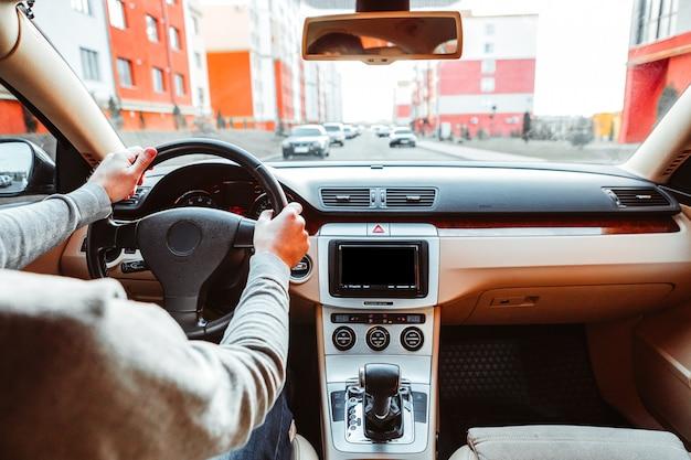 アスファルトの道路で現代の車を運転する若い男