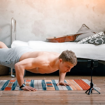 청년은 집에서 운동하러 간다. 금발 머리를 가진 쾌활한 운동가는 팔 굽혀 펴기를하고 침실에서 블로그를 촬영하고 옆에 온라인 교육이있는 전화가 있습니다.