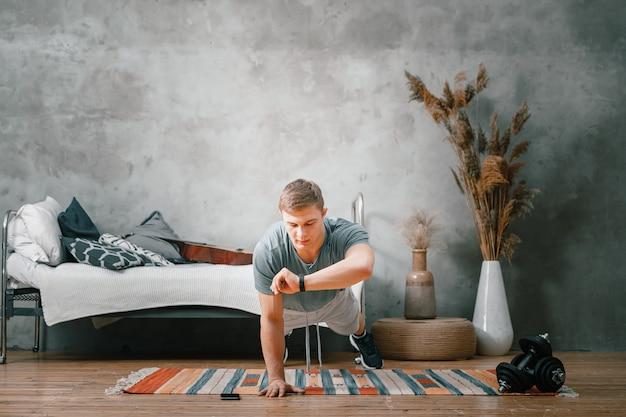 Молодой человек занимается спортом дома. веселый спортсмен со светлыми волосами держит доску и смотрит на секундомер в часах на руке в спальне