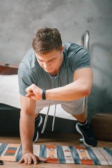 その青年は家でスポーツに出かける。ブロンドの髪の陽気なスポーツマンは、板を保持し、寝室で彼の手で時計のストップウォッチを見ています