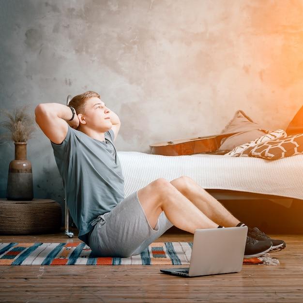 청년은 집에서 운동하러 간다. 금발 머리를 가진 쾌활한 운동가가 침실에서 언론을 만들고 옆에 온라인 교육이 가능한 노트북이 있습니다.