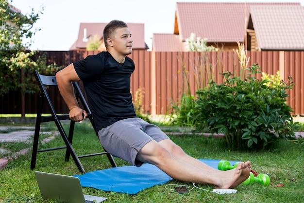 Юноша занимается спортом дома на заднем дворе в летний день. веселый спортивный мужчина качает бицепс, отжимается на стуле, есть в ноутбуке, гантели.