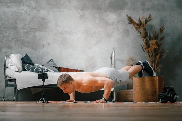 その青年は家でスポーツに出かける。アスリートは腕立て伏せをして映画を見たり、寝室の電話から勉強したり、背景にはベッド、花瓶、カーペットを置いたりします。