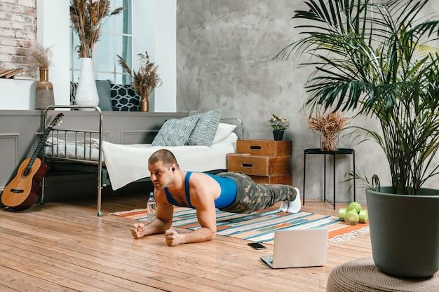 Молодой человек занимается спортом дома