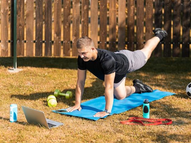 若い男は外でスポーツに出かける。ブロンドの髪の陽気なスポーツマンは庭の芝生に突進します、隣にはオンライントレーニング付きのラップトップがあります