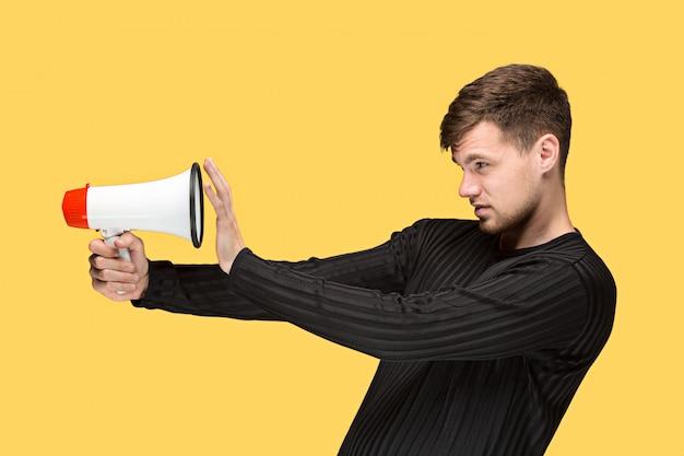 Молодой человек держит мегафон