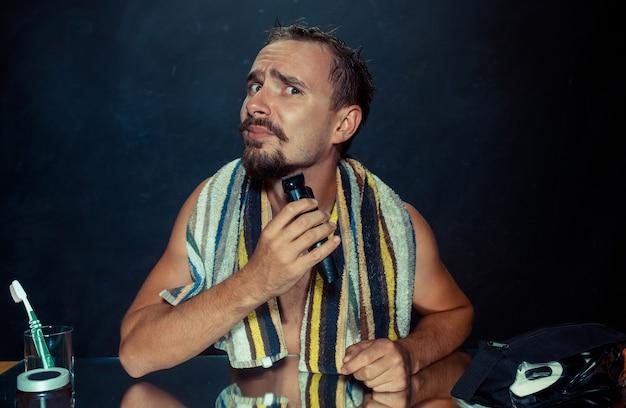 집에서 그의 수염을 긁적 거울 앞에 앉아 침실에서 젊은 남자. 인간의 감정과 라이프 스타일 개념