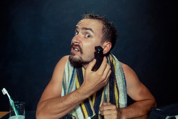 Молодой человек в спальне сидит перед зеркалом, почесывая бороду дома. человеческие эмоции и концепция образа жизни