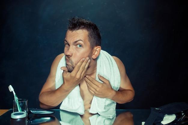 Молодой человек в спальне сидит перед зеркалом, почесывая бороду дома. концепция человеческих эмоций и проблемы с волосами