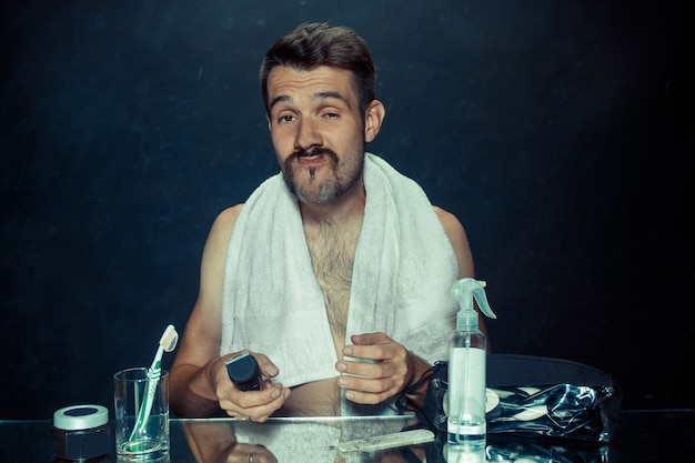 鏡の前に座っている寝室の若い男が自宅でひげを掻いている。人間の感情の概念と皮膚の問題