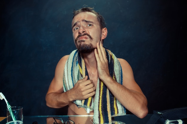 鏡の前に座っている寝室の若い男が自宅でひげを掻いている。人間の感情の概念