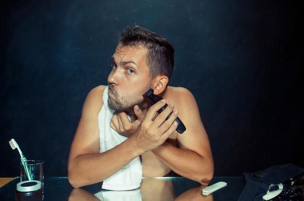 Молодой человек в спальне сидит перед зеркалом, почесывая бороду дома. концепция человеческих эмоций