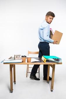 Молодой человек уволен и складывает на рабочем месте вещи, папки, документы. не справлялся с обязанностями. концепция проблем офисного работника, бизнеса, рекламы, отставки.