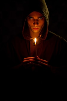 若い男は暗闇を照らす古いキャンドルを持っています。