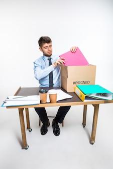 Молодой человек ушел в отставку и складывает вещи на рабочем месте
