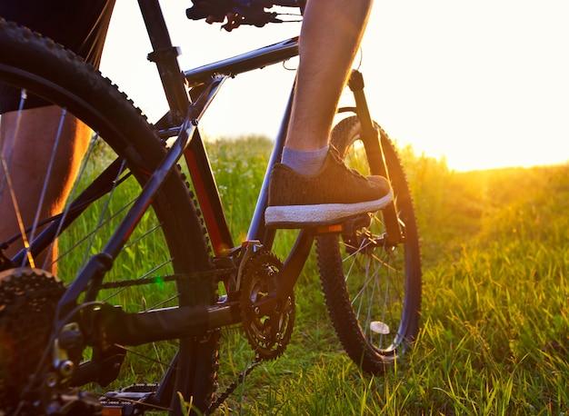 Молодой человек едет на велосипеде по дорожке с большим количеством травы и цветов посреди поля.