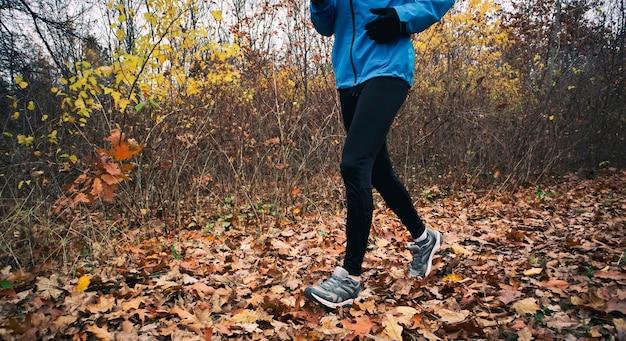 젊은 남자가 가을 공원을 통로로 달리고 있습니다.