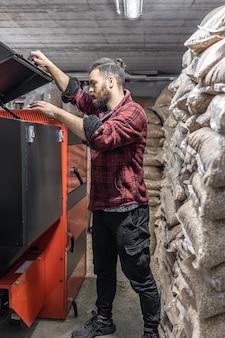 Молодой человек смотрит в твердотопливный котел, работает на биотопливе, экономное отопление.