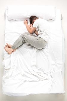 白いベッド、トップビューで横になっている若い男
