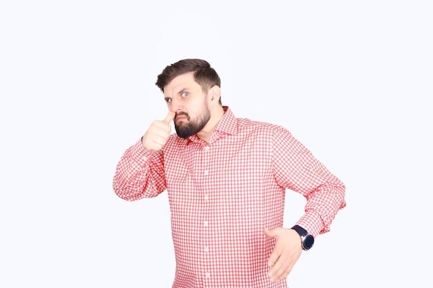 Молодой человек поднял руку к лицу. бородатый мужчина в розовой клетчатой рубашке на белом фоне