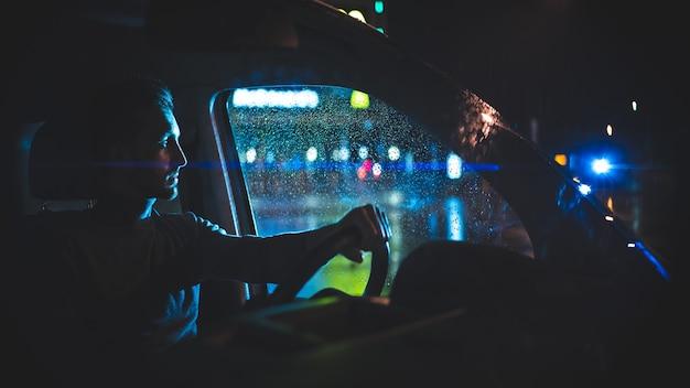 젊은 남자는 밤 비오는 거리에 차에 앉아