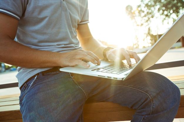モールの近くのベンチに座って、ラップトップで作業している若い男