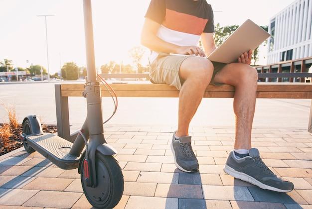 モールの近くで電動スクーターを持ってベンチに座って、ラップトップで作業している若い男