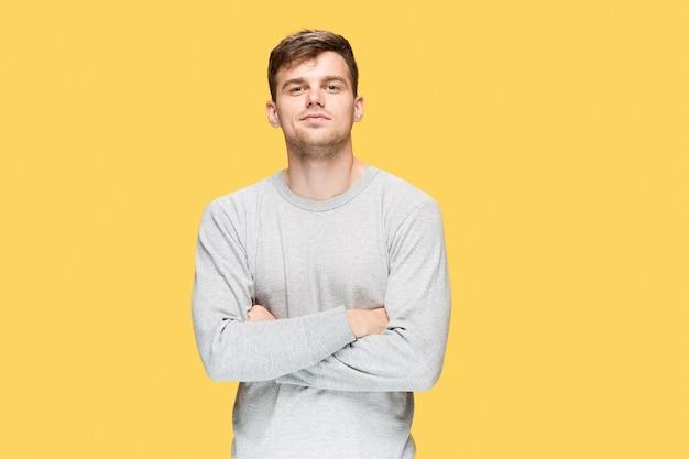 笑みを浮かべて、黄色のスタジオの背景にカメラを見て若い男